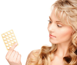 woman looking at pills for acne